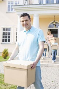 Portrait of man carrying cardboard box while moving house with family in background